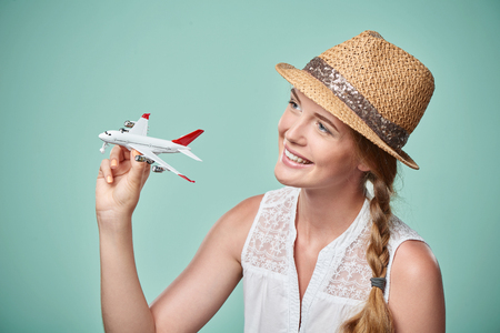 portait: Closeup portrait of beautiful woman in straw hat holding airplane model in hand, dreaming about holidays