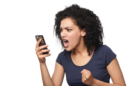 Angry mixed race caucasian - african american woman shouting in mobile phone, over white background Stock Photo