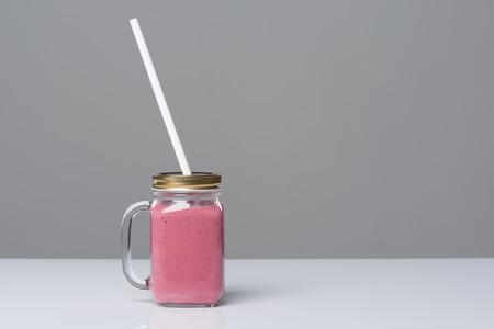 vaso de precipitado: Taza del vaso del tarro con la bebida rosada del smoothie en la tabla