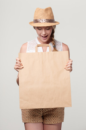 Beautiful excited surprised woman wearing summer straw fedora hat holding craft bag with empty copy space looking down at it