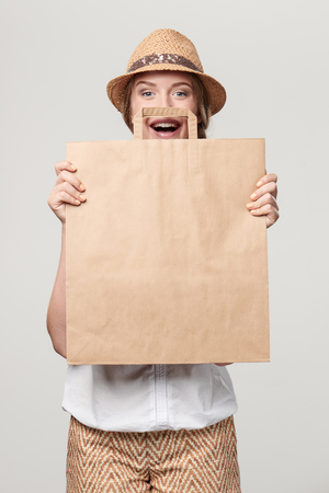 Happy playful woman wearing summer straw fedora hat holding craft bag with empty copy space Stock Photo