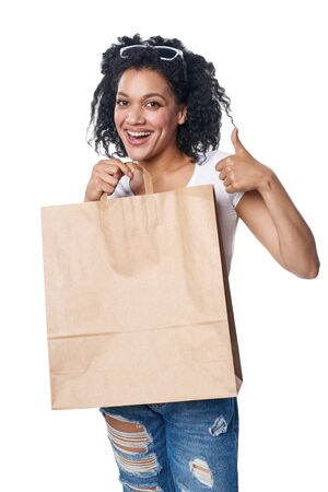 Happy mixed race woman holding craft shopping bag with empty copy space and gesturing thumb up Stock Photo