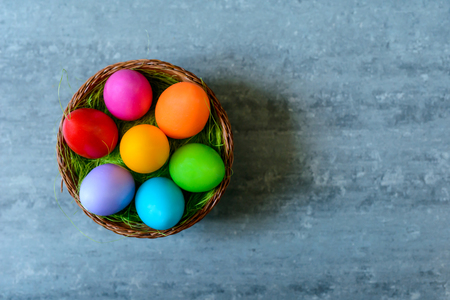 Top view of multicolored Easter eggs in a basket on grey concrete background