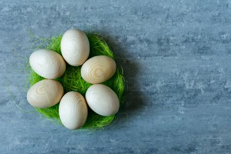 Top view of wooden eggs on grey concrete background