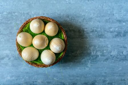 Top view of wooden Easter eggs in a basket on grey concrete background Stock Photo