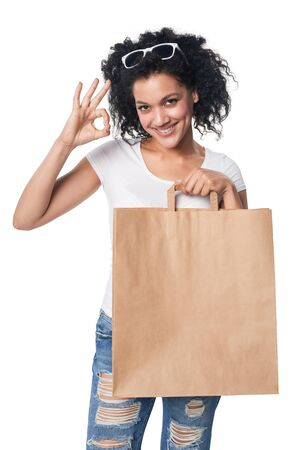 Happy mixed race woman holding craft shopping bag with empty copy space and gesturing OK sign Stock Photo