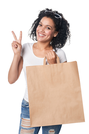 Happy mixed race woman holding craft shopping bag with empty copy space and gesturing V hand sign