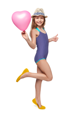 Full length child girl in swimsuit and summer hat with pink balloon heart shape gesturing thumb up, studio portrait Stock Photo