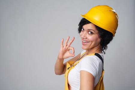 De glimlachende gemengde vrouw die van de rasbouw geel draagt beschermt helm en het algehele tonende OK gebaar over schouder, over grijze achtergrond