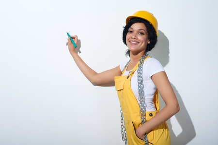 blank space: Happy smiling mixed race construction woman wearing yellow protect helmet and overall holding a pen going to write on white blank copy space Stock Photo