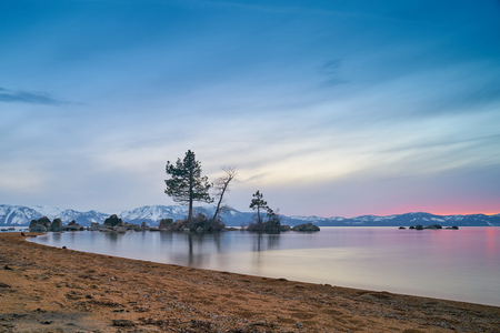 Sunset at Lake Tahoe with sand beach, mountains covered by snow at background Stock Photo