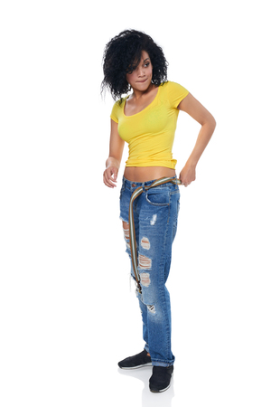 put away: Full length funky female in distressed jeans putting on the belt over white background