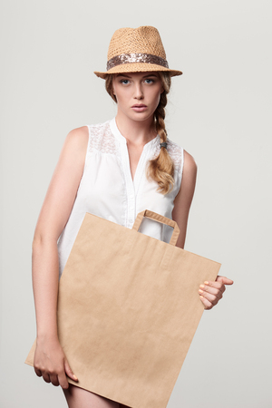Beautiful fashion woman holding craft shopping bag with empty copy space