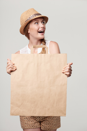 Beautiful excited woman wearing summer straw hat holding craft shopping bag with empty copy space and looking away Stock Photo