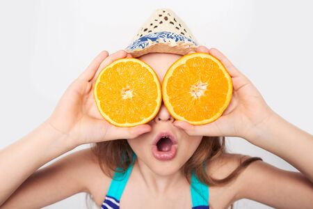 Llittle girl in swimsuit and summer hat having fun with half oranges making fake eyeglasses with expression of surprise, search concept