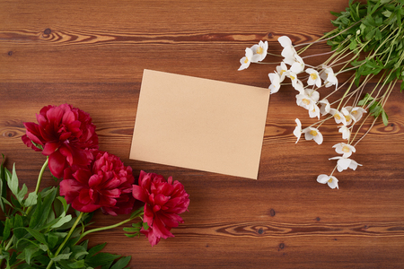 blank space: Top view craft envelope with blank copy space for text and spring flowers on wooden background Stock Photo