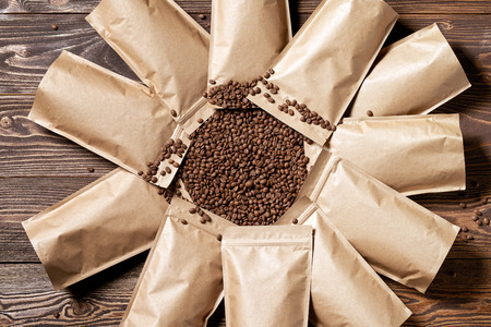 Many mock-up craft paper pouch bags top view over wooden background with coffee beans in the center