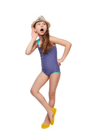 tattle: Surprised full length child girl in swimsuit and summer hat with hand on ear listening, over white background
