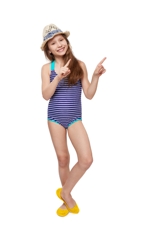 Full length child girl in swimsuit and summer hat pointing to the side at blank copy space, over white background Stock Photo