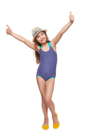 Full length child girl in swimsuit and summer hat giving double thumb up, over white background