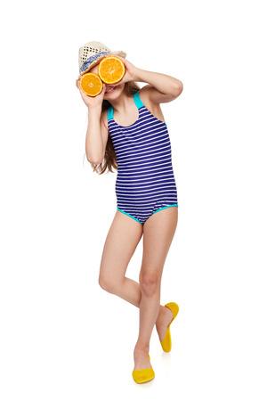 Llittle girl in swimsuit and summer hat having fun with half oranges making fake eyeglasses, over white background, full length portrait