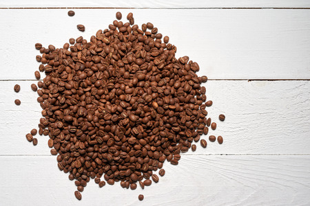 Roasted brown coffee beans over white wooden table, top view background Stock Photo