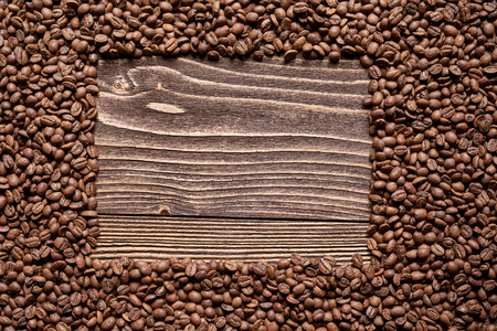 scattering: Roasted brown coffee beans on rough wooden table with blank copy space for text in form of rectangle Stock Photo