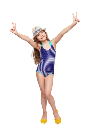 Full length child girl in swimsuit and summer hat giving double V signs, over white background