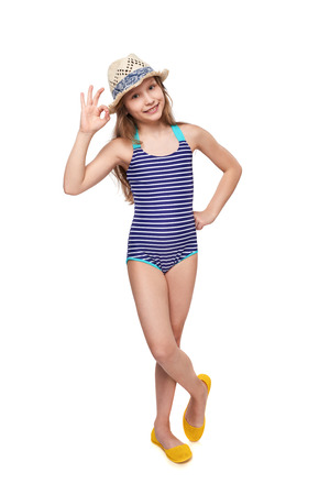 Full length child girl in swimsuit and summer hat gesturing OK sign, over white background