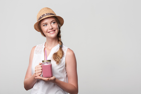Smiling girl holding jar tumbler mug with pink smoothie drink, looking at blank copy space Фото со стока