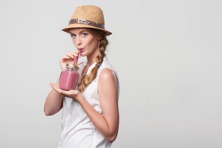 vaso de precipitado: Chica sonriente con vaso jarra taza de beber a través de paja una bebida de smoothie de color rosa, retrato sobre fondo gris con copia espacio en blanco