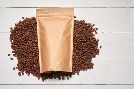 モックアップ クラフト ペーパー ポーチ バッグ トップ ビュー × コーヒー豆で横になっている白い木製のテーブルの上 写真素材