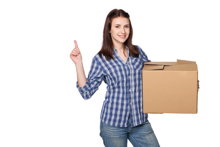 Delivery, relocation and unpacking. Smiling young woman holding cardboard box and pointing finger up at blank copy space, isolated on white background Stock Photo