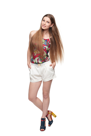 Beautiful full length female in shorts and top with long hair fluttering on wind, isolated on white background