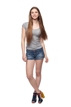Beautiful full length female in denim shorts and grey tshirt with long hair, isolated on white background