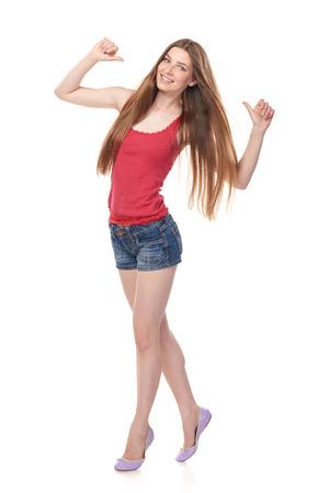 In voller Länge von lächelnder langbeiniger junger Frau in den Denimkurzen hosen und in roter Spitze Finger auf, lokalisiert auf weißem Hintergrund zeigend Standard-Bild - 81280095