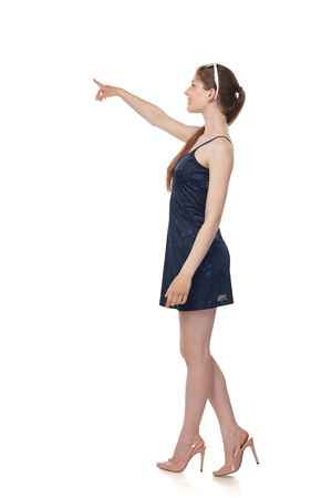 Beautiful casual young woman isolated on white background in full length standing in profile pointing or pushing something with index finger. Stock Photo
