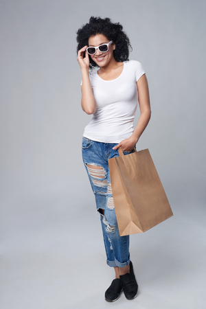 Full length happy fashionable woman holding craft shopping bag with empty copy space on grey background