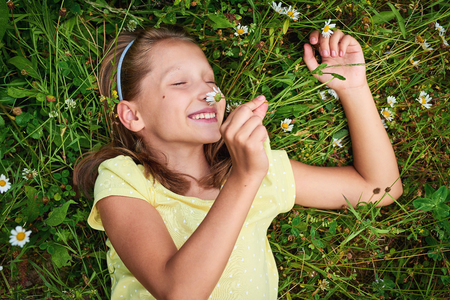 careless: Top view little happy girl lying in summer meadow between camomiles smelling the flower enjoying with closed eyes