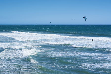 Remote view at kite surfers riding the waves in Santa Cruz, California