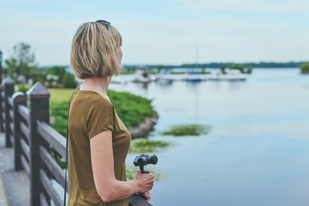 Woman enjoying view in a park, holding small personal camera in hands