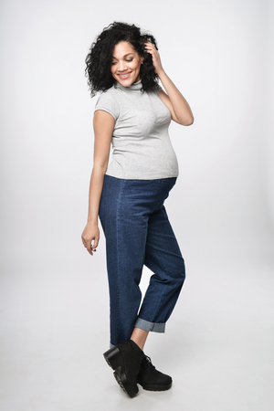 Pregnant woman standing in full length smiling posing, over white background Stock Photo