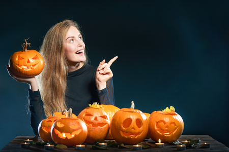 Happy excited woman with Halloween pumpkins over dark background pointing finger at blank copy space