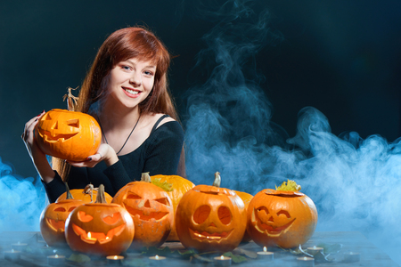 Happy smiling red haired woman with Halloween pumpkins over smoky background