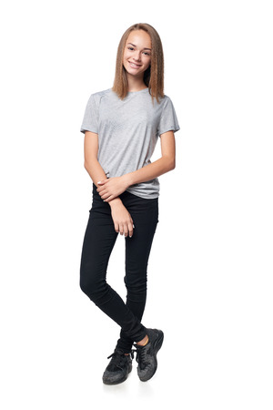Teen girl in full length standing casually smiling at camera, isolated on white background