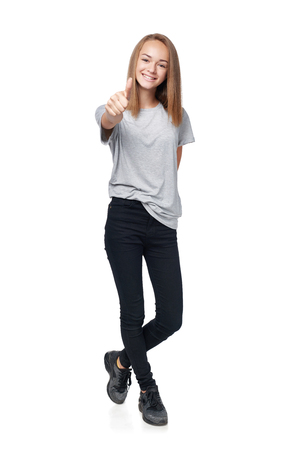 Teen girl in full length showing thumb up sign, isolated on white background