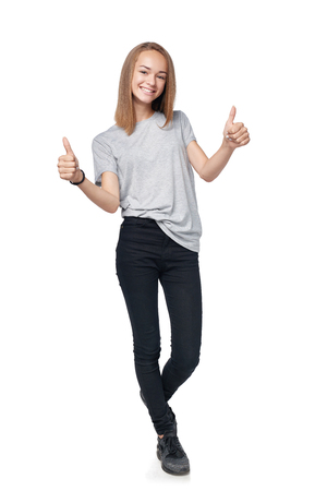 Teen girl in full length giving double thumb up sign, isolated on white background Stock Photo