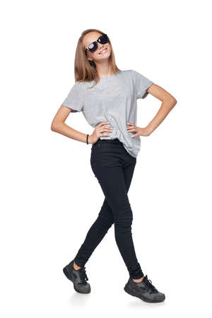 Teen girl in sunglasses in full length standing casually smiling at camera, isolated on white background Stock Photo