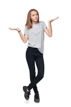 Twijfelachtig tienermeisje die zich in volledige lengte met twee geopende handpalmen bevinden die met lege exemplaarruimten het wegen kiezen, geïsoleerd op witte achtergrond overweegt Stockfoto