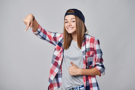 Teen girl pointing to the side down at empty copy space and gesturing thumb up, over grey background